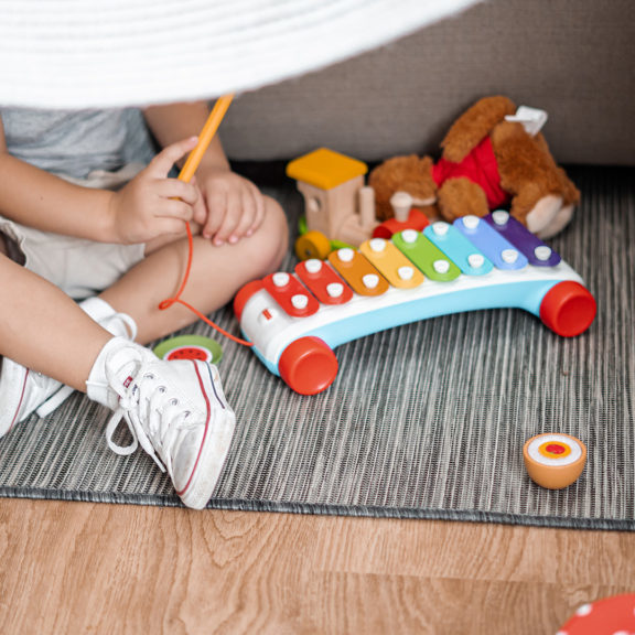 child-sitting on-floor-and-playing-with-xylophone-toy